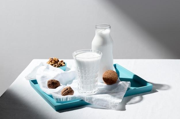 Ângulo alto do copo de leite e garrafa com nozes