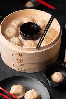 Ângulo alto do prato tradicional asiático com bolinhos e palitos
