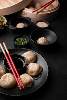 Ângulo alto do prato tradicional asiático com bolinhos e pauzinhos