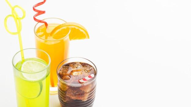 Ângulo alto dos copos com refrigerantes e canudos