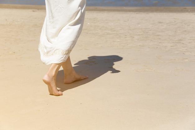 Ângulo baixo atrás de uma mulher caminhando descalça na praia