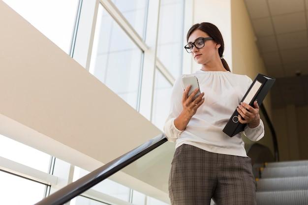Ângulo baixo da empresária segurando a pasta e trabalhando no smartphone