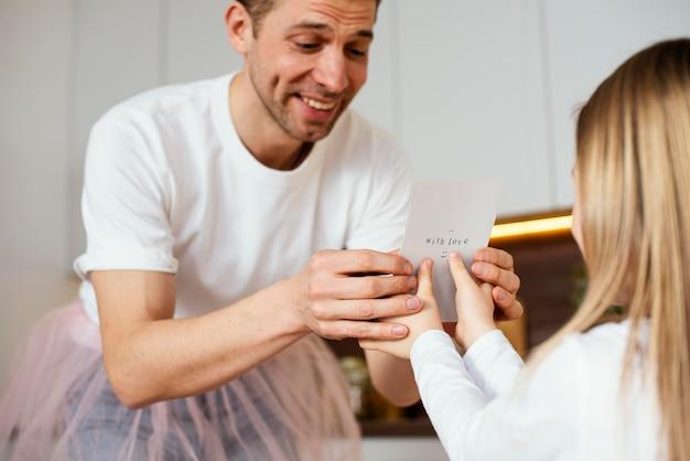 Ângulo baixo da menina dando um cartão do dia dos pais para o pai