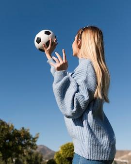 Ângulo baixo da menina pegando bola de futebol