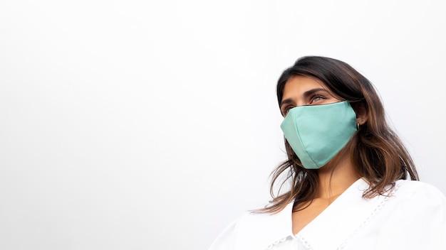 Ângulo baixo da mulher com máscara facial e espaço de cópia