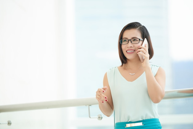 Ângulo baixo da mulher de negócios, falando ao telefone