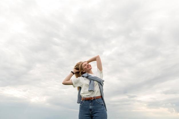Ângulo baixo da mulher posando ao ar livre
