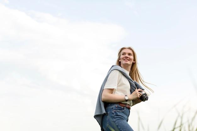 Ângulo baixo da mulher posando enquanto segura a câmera