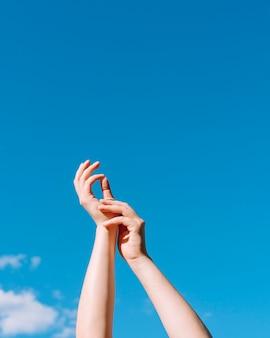Ângulo baixo das mãos levantadas com o céu e o espaço da cópia