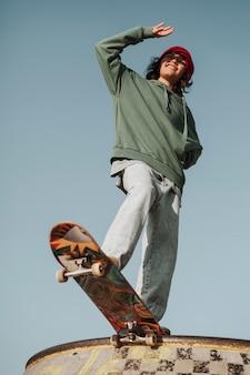 Ângulo baixo de adolescente no skatepark se divertindo