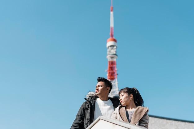 Ângulo baixo de casal apreciando a vista da cidade com antena na parte de trás