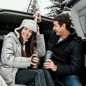 Ângulo baixo de casal feliz tomando uma bebida quente no porta-malas do carro e brincando durante uma viagem