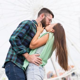 Ângulo baixo de casal romântico se beijando ao ar livre