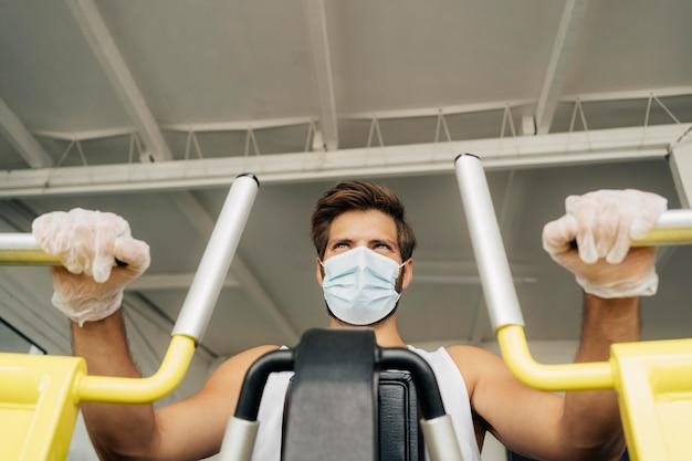 Ângulo baixo de homem com máscara médica malhando na academia