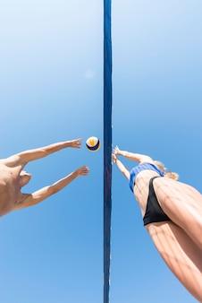 Ângulo baixo de jogadores de vôlei tentando pegar a bola por cima da rede