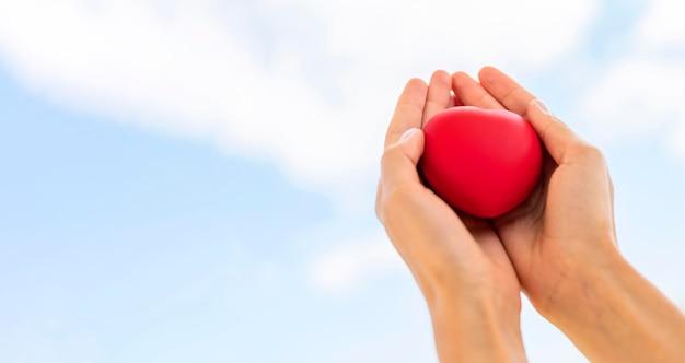 Ângulo baixo de mãos segurando um formato de coração com espaço de cópia