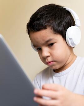 Ângulo baixo de menino usando laptop com fones de ouvido