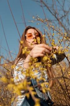Ângulo baixo de mulher com óculos de sol posando com flores