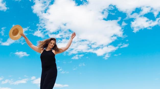 Ângulo baixo de mulher, desfrutando de um belo dia com céu e nuvens