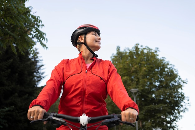 Ângulo baixo de mulher idosa andando de bicicleta ao ar livre