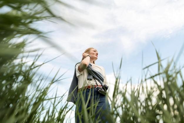 Ângulo baixo de mulher posando com grama
