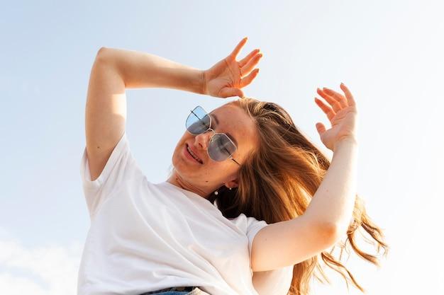 Ângulo baixo de mulher posando enquanto aproveita o tempo ao ar livre