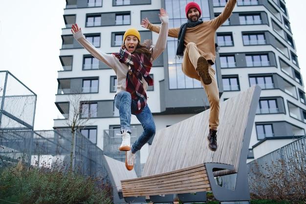 Ângulo baixo de proprietários de jovens casais alegres pulando ao ar livre na frente de um novo apartamento