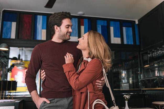 Ângulo baixo de um casal alegre e satisfeito se abraçando e olhando um para o outro