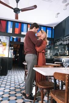 Ângulo baixo de um lindo casal atraente olhando um para o outro e em pé