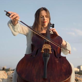 Ângulo baixo de uma musicista tocando violoncelo ao ar livre