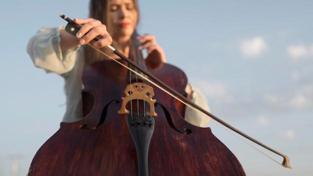 Ângulo baixo de uma musicista tocando violoncelo