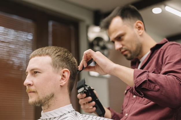 Ângulo baixo do cabeleireiro dando um corte de cabelo
