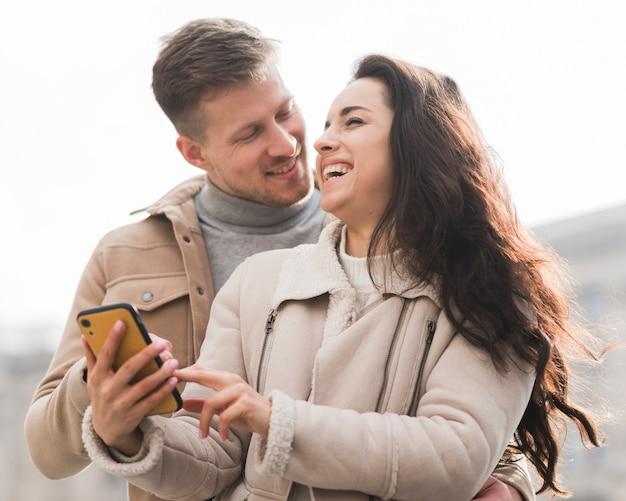 Ângulo baixo do casal sorridente segurando smartphone