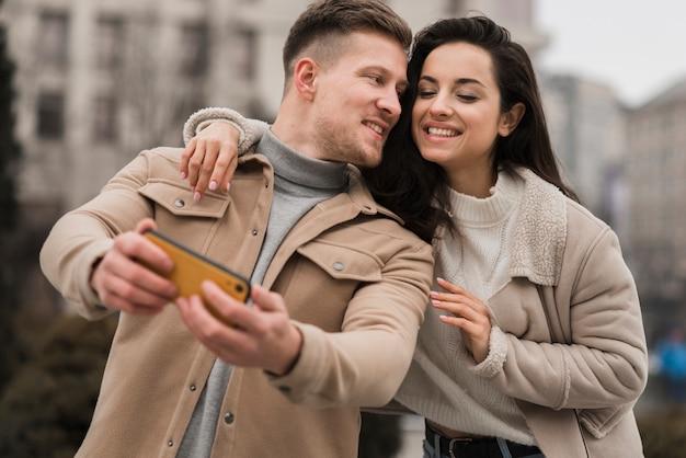 Ângulo baixo do casal tomando uma selfie