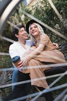 Ângulo baixo do casal visto através de raios de bicicleta
