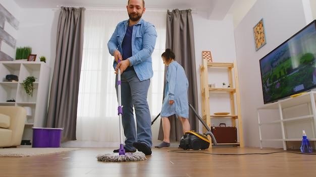 Ângulo baixo do homem limpando o chão da sala com o esfregão.