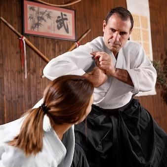 Ângulo baixo do instrutor de artes marciais masculino treinando com a estagiária na sala de prática