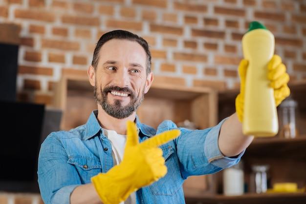 Ângulo baixo do limpador gay masculino apontando para o limpador enquanto o segura e olha para ele