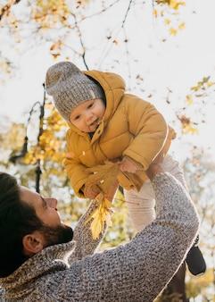 Ângulo baixo do pai e do bebê ao ar livre