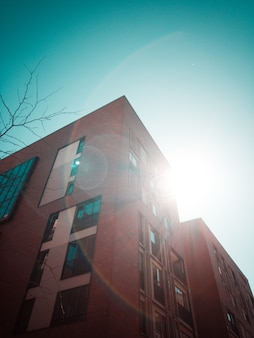 Ângulo baixo do prédio de apartamentos e o sol atrás dele