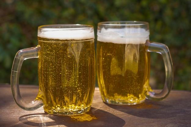 Ângulo baixo duas canecas com cerveja fresca