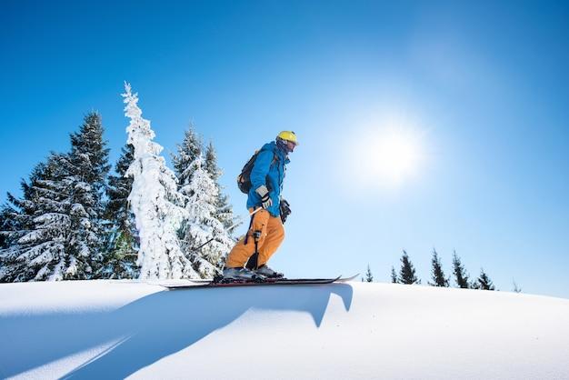 Ângulo baixo e comprimento total de um esquiador no topo da montanha, aproveitando o lindo dia ensolarado de inverno