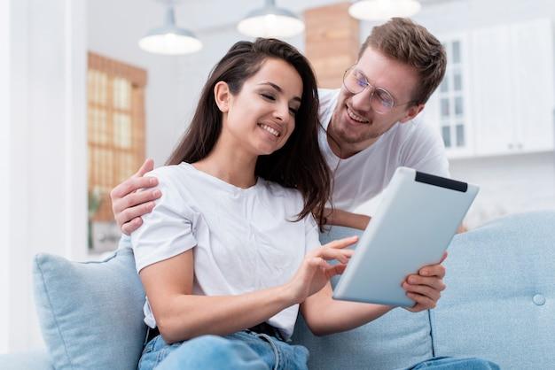 Ângulo baixo homem e mulher olhando no seu tablet