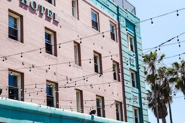 Ângulo baixo tiro de um edifício de hotel com luzes da rua e amd palmas no fundo