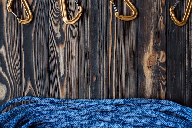 Ângulo de visão diferente. equipamento de escalada isolado. parte do mosquetão deitado sobre a mesa de madeira.