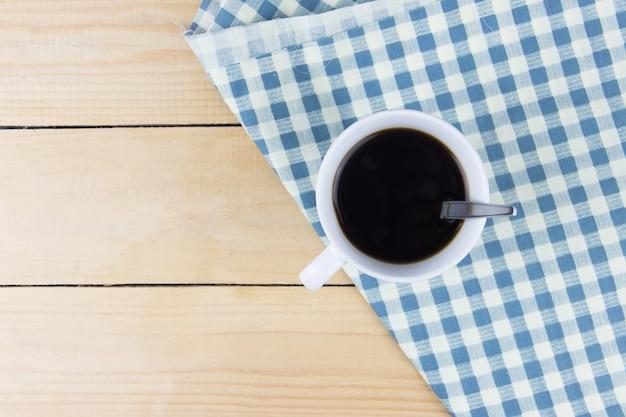 Ângulo de vista superior do café quente no guardanapo branco e azul Foto Premium