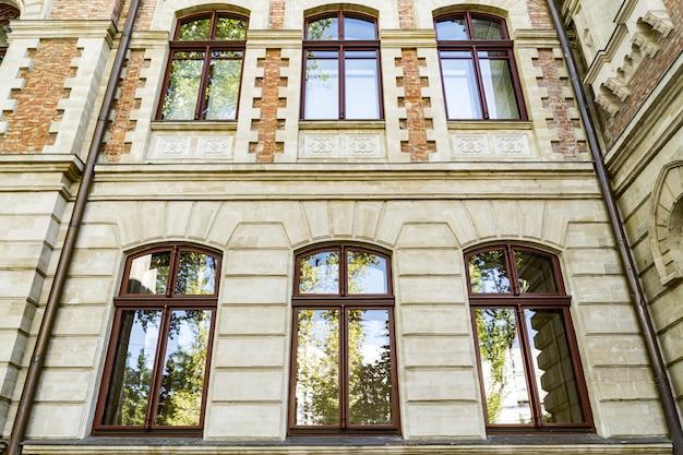 Ângulo para baixo das janelas em arco em um belo prédio antigo com o reflexo do céu e das árvores no vidro