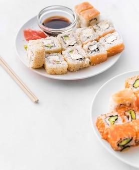 Ângulo tiro placas de sushi com molho de soja