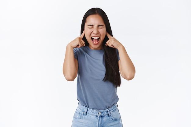 Angustiada e farta de uma adolescente asiática com longos cabelos escuros, gritando perdendo a paciência, não consigo controlar as emoções, fecha os olhos e grita, fecha as orelhas com os dedos, não suporto as pessoas brigando ao seu redor