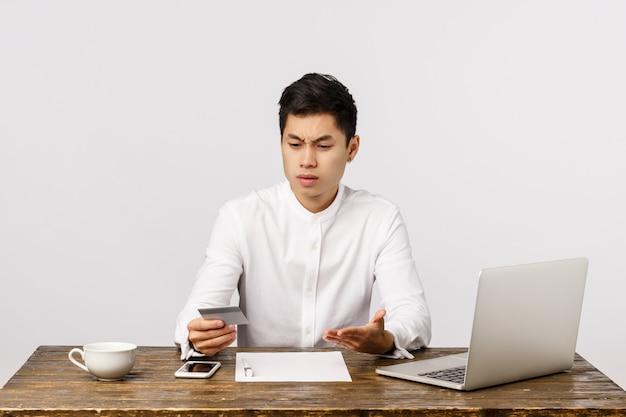 Angustiado, questionado e frustrado rapaz asiático sentado no escritório, no trabalho, com documentos e laptop, olhando para o cartão de crédito e reclamando de transações estranhas,